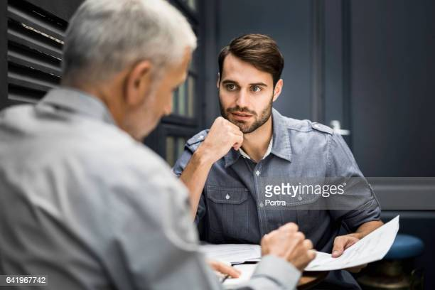 Businessmen discussing over documents in office