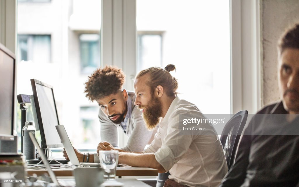 Businessmen discussing over laptop in office : Stock Photo