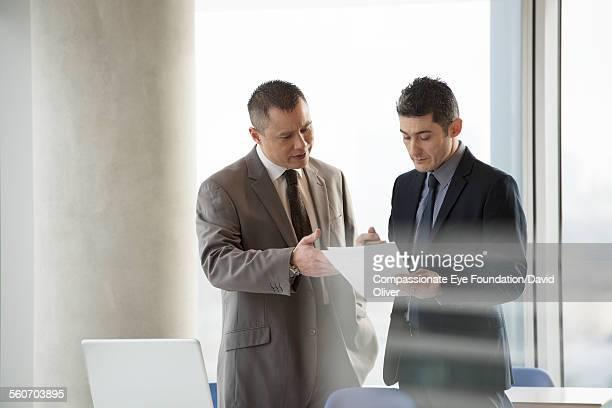 """businessmen discussing paperwork in office - """"compassionate eye"""" stockfoto's en -beelden"""