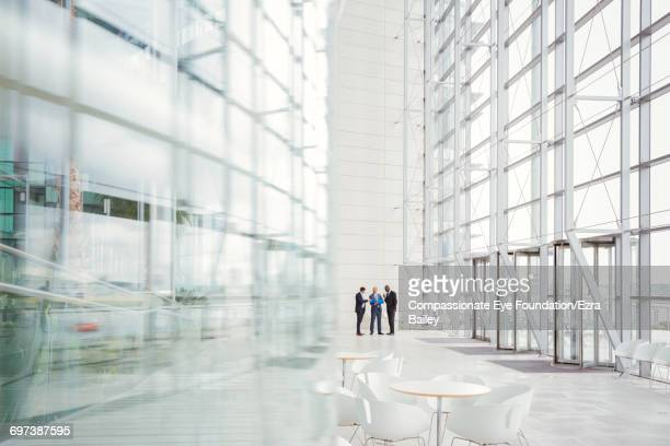 businessmen discussing plans in modern lobby - brightly lit stock pictures, royalty-free photos & images