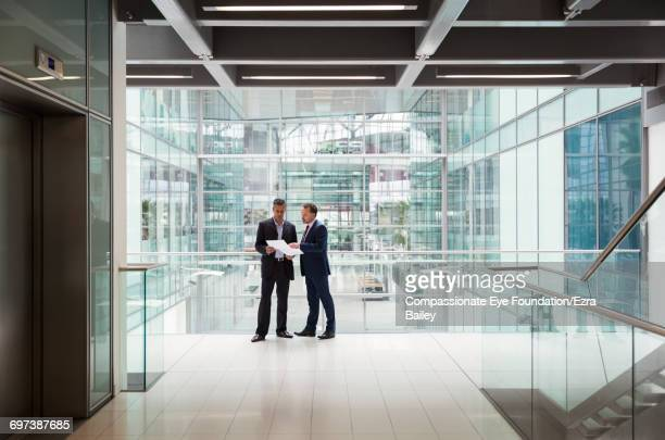 Businessmen discussing plans in office hallway