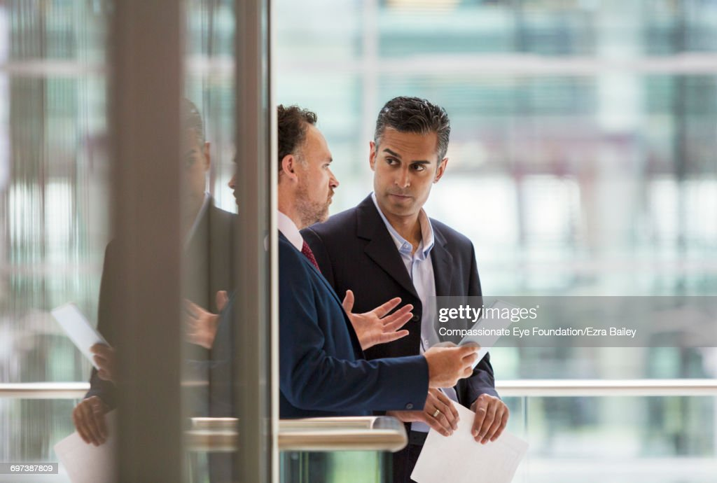 Businessmen discussing project on office balcony : Stock Photo