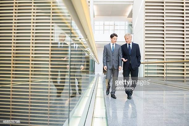 Businessmen Discussing While Walking In Office