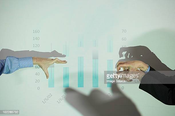 Businessmen doing shadow puppets in front of whiteboard