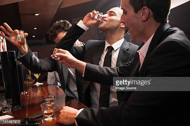 businessmen drinking shots in bar - binge drinking stock photos and pictures