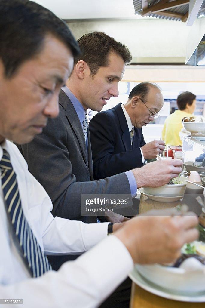 Businessmen eating : Stock Photo