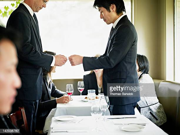 Businessmen exchanging business card in restaurant