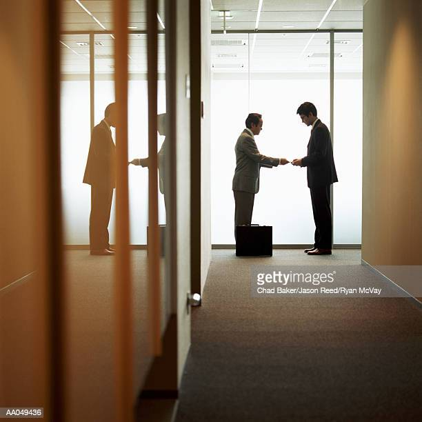 Businessmen exchanging business cards in office hallway, side view