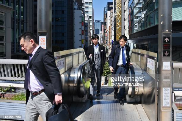 Businessmen exit an escalator in Tokyo's Ginza district on April 3 2019 For the Emperor's abdication on April 30 Japanese workers will enjoy an...