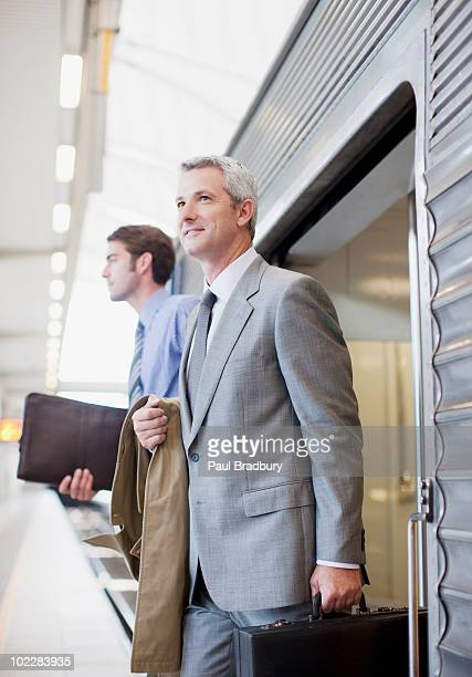 Businessmen exiting train in train station