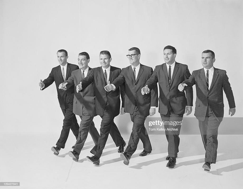 Businessmen extending hand to shake, smiling : Stock Photo