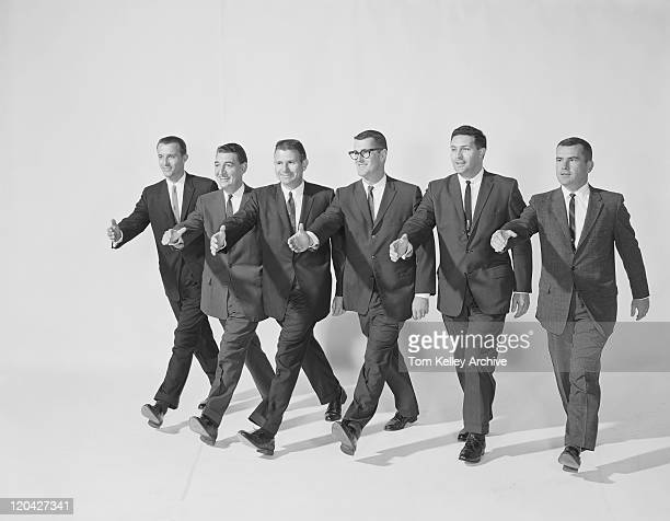 businessmen extending hand to shake, smiling - archival bildbanksfoton och bilder