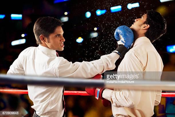 businessmen fighting in boxing ring - colpire foto e immagini stock