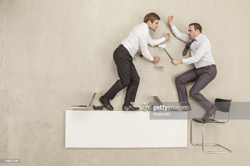 Businessmen fighting in office : Stock Photo