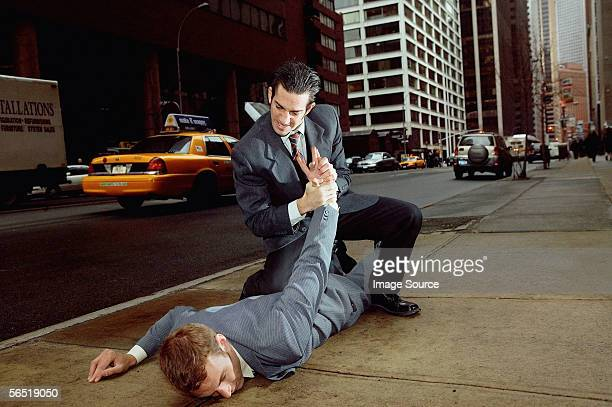 Businessmen fighting in street