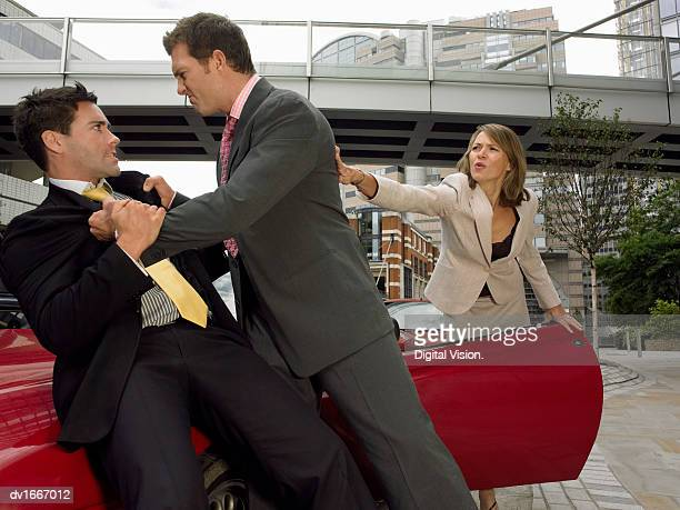 Businessmen Fighting on the Bonnet of a Sports Car and a Businesswoman Stopping Them