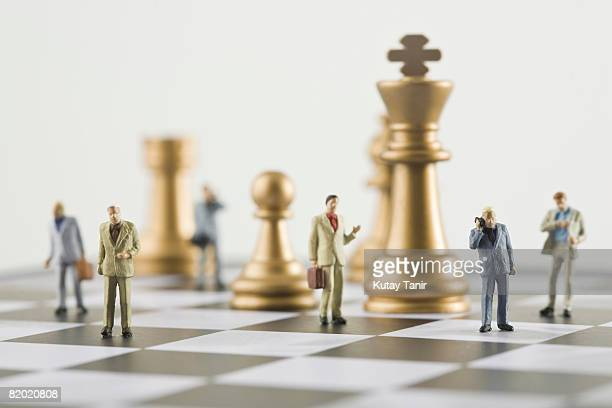 Businessmen figurines standing a top chess board (focus on foreground)