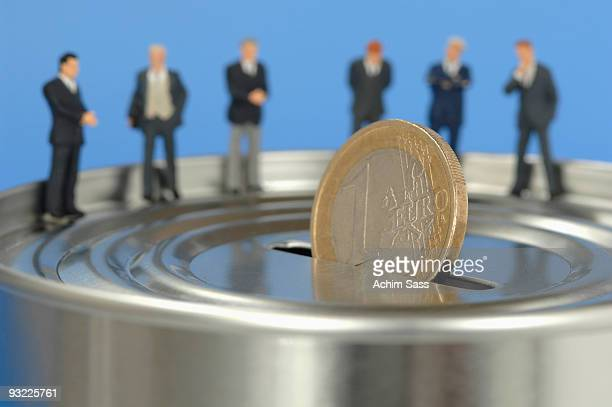 Businessmen figurines standing on money box, close-up