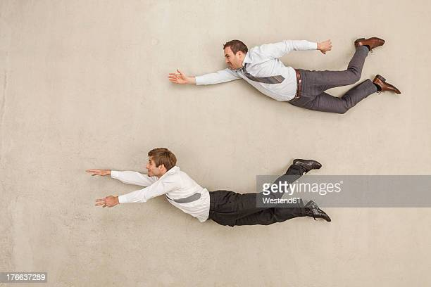 businessmen flying against beige background - fliegen stock-fotos und bilder