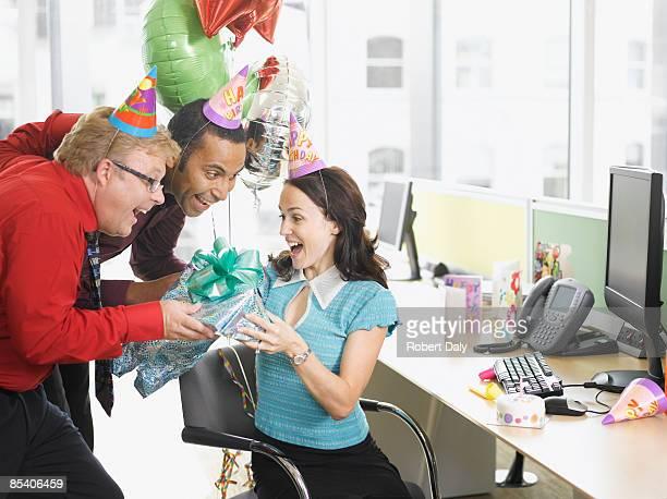 Empresarios dando regalos de cumpleaños para colega