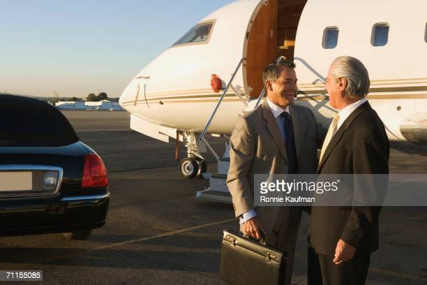 Businessmen greeting each other on airplane runway