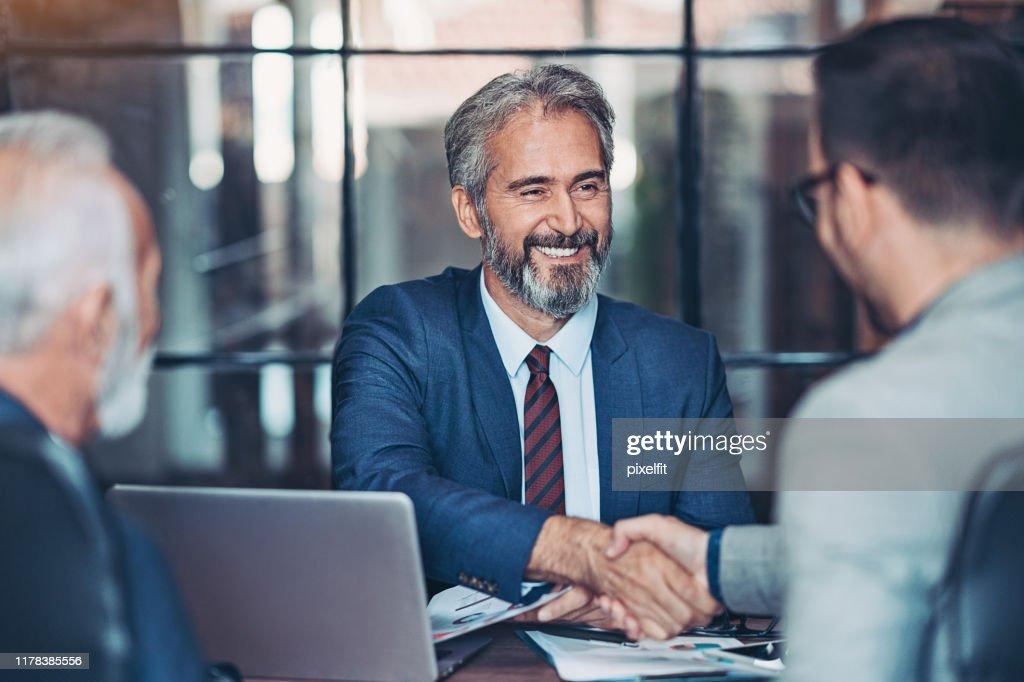 Businessmen handshake in the office : Stock Photo