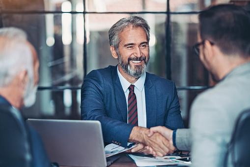 Businessmen handshake in the office 1178385556