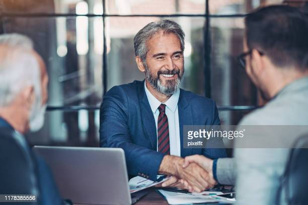 businessmen handshake in the office - business imagens e fotografias de stock