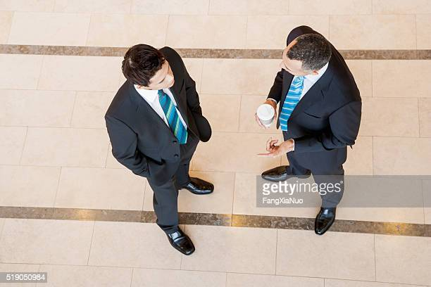 businessmen having a conversation - hands in pockets stock photos and pictures