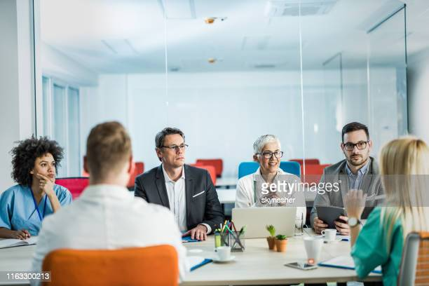 businessmen having a meeting with team of doctors in the office. - doctor's surgery stock pictures, royalty-free photos & images