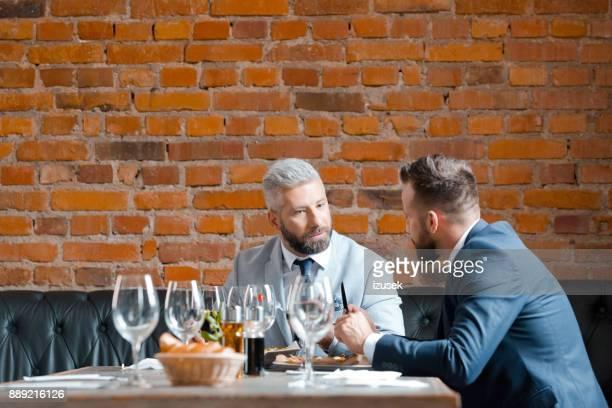 ondernemers hebben zakelijke lunch in restaurant - izusek stockfoto's en -beelden