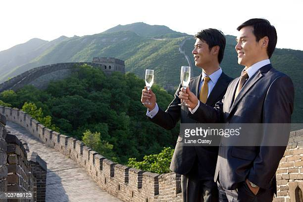 Businessmen having champagne on the Great Wall