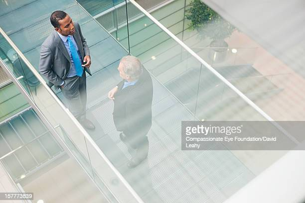 Businessmen having meeting on atrium balcony