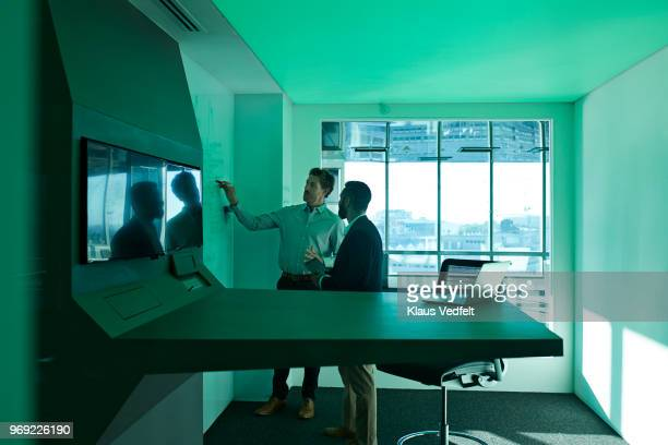 Businessmen having standing meeting inside futuristic meeting room