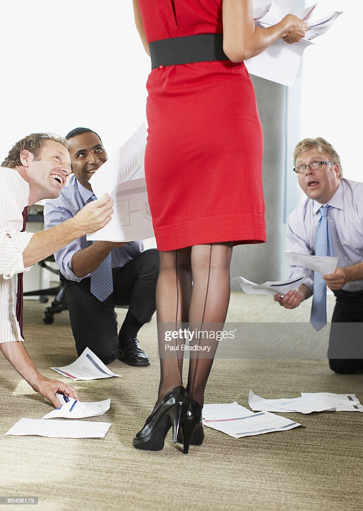 Businessmen  helping sexy co-worker : Stock Photo