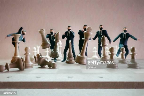 geschäftsleute schlagen schachfiguren - bestimmtheit stock-fotos und bilder