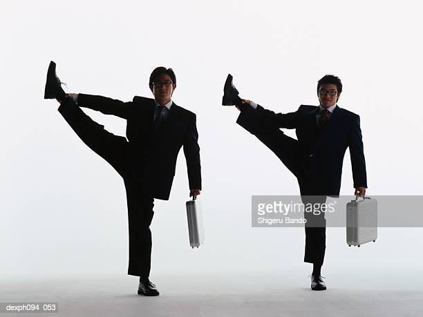 businessmen hold their legs high into the air - 足を開く ストックフォトと画像