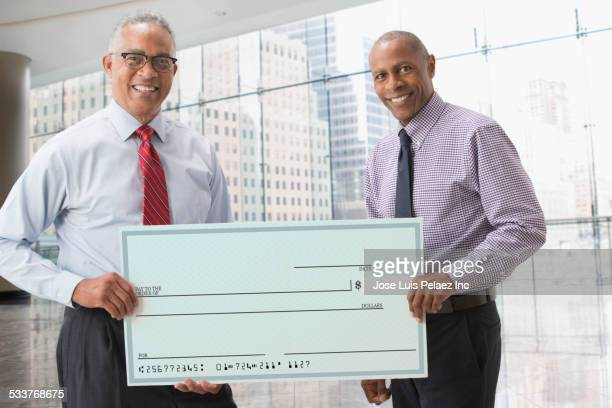 Businessmen holding blank check in office
