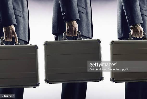 Businessmen holding briefcases