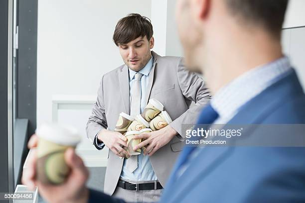 Businessmen holding coffee cups to go for all