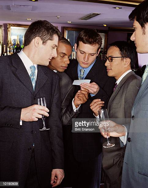 Businessmen holding empty glasses looking at business card