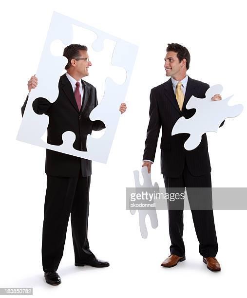 Geschäftsleute halten Puzzle Peices auf Weiß