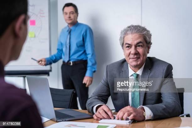 Ein Geschäftsmann hört zu währrend der andere etwas auf dem Flipchart verdeutlicht
