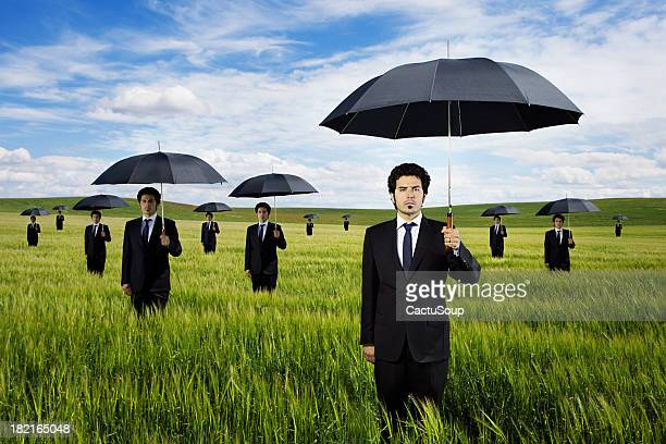 Businessmen in a green field with umbrella