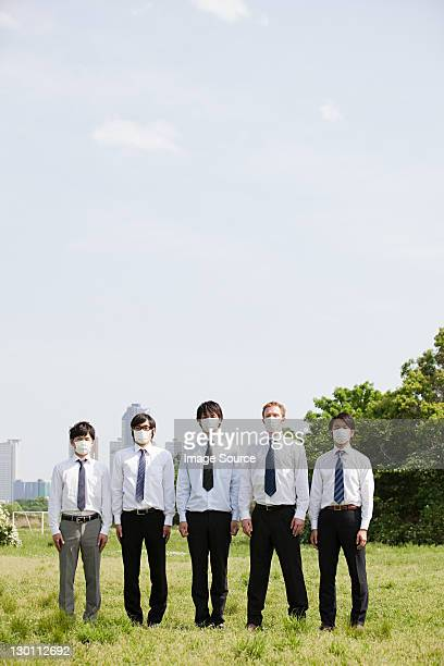 Businessmen in a row wearing pollution masks