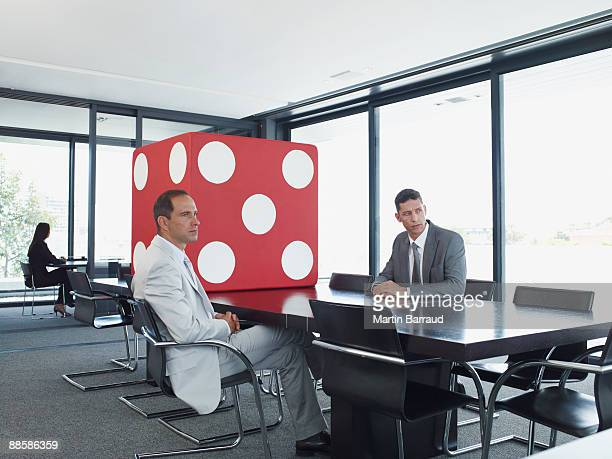 Businessmen in conference room with giant dice