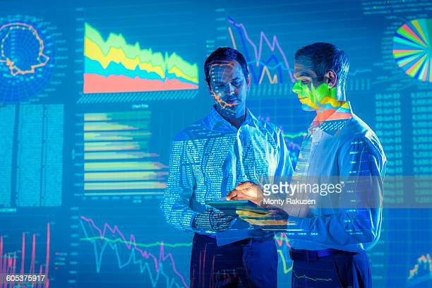 Businessmen in conversation with projected graphical financial data