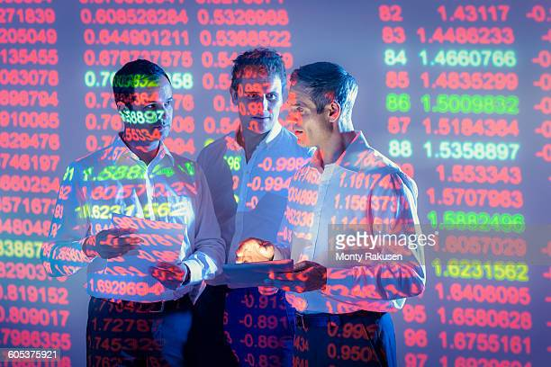 businessmen in conversation with projected graphical financial data - buntes hemd stock-fotos und bilder