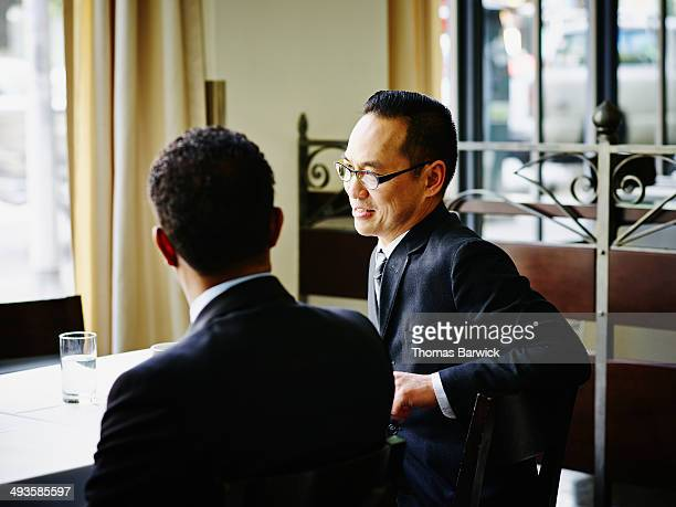 Businessmen in discussion at table in restaurant