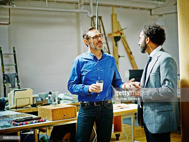 Businessmen in discussion drinking coffee